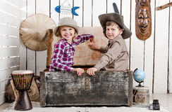 Two little children study map on the wall. Two little children in sitting in old chest study map on the wall Royalty Free Stock Photo
