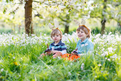 Two little children wearing Easter bunny ears and eating chocola Stock Images