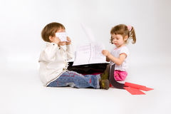 Two little chuldren playing with papers Royalty Free Stock Photo