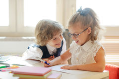 Two little classmate, laddie and girlie, are sitting at the same desk. Royalty Free Stock Photos