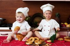 Two little cooks. Two little boys in the cook costumes at the kitchen sitting on the table Royalty Free Stock Photo