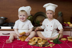 Two little cooks. Two little boys in the cook costumes sitting on the table Stock Photography