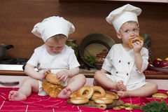 Two little cooks. Two little boys in the cook costumes at the kitchen sitting on the table Royalty Free Stock Photography