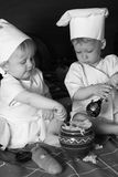 Two little cooks. Two little boys in the cook costumes at the kitchen sitting on the table. Black and white photo Royalty Free Stock Image
