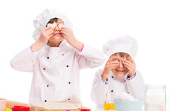 Two little cooks holding pieces of dough like eyes Royalty Free Stock Images
