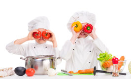 Two little cooks playing vegetables for soup Royalty Free Stock Photography