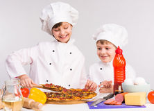 Two little cooks portioning cooked pizza Royalty Free Stock Photo