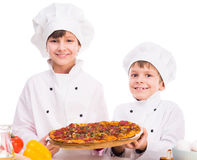 Two little cooks portioning cooked pizza Stock Images