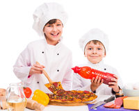 Two little cooks portioning cooked pizza Stock Photo