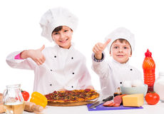 Two little cooks portioning cooked pizza Royalty Free Stock Image