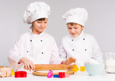 Two little cooks rolling out a dough Stock Image
