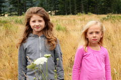 Two little country girls. Two little blond country girls standing in a field of tall grass and wild flowers. Shallow depth of field Stock Photos