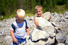 Two little cute boys together building tower of stones Royalty Free Stock Photography