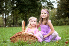 Two little cute girlfriend in beautiful dresses are laughing in the sum Royalty Free Stock Image
