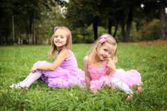 Two little cute girlfriend in beautiful dresses are laughing in the sum Stock Photography
