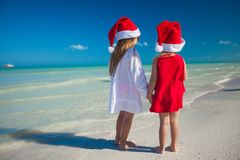 Two little cute girls in Christmas hats have fun Stock Photos