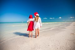 Two little cute girls in Christmas hats have fun. On the exotic beach. This image has attached release Royalty Free Stock Photo