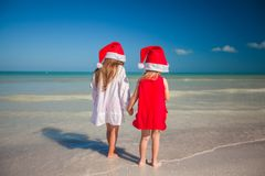 Two little cute girls in Christmas hats have fun Royalty Free Stock Image