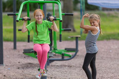 Two little cute girls is engaged in sports equipment Stock Images