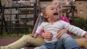 Two little cute girls having great fun while riding down slide in the playground. HD stock video footage