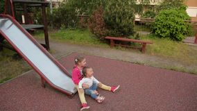 Two little cute girls having great fun while riding down slide in the playground stock video footage