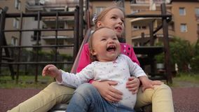 Two little cute girls having great fun while riding down slide in the playground. HD stock footage