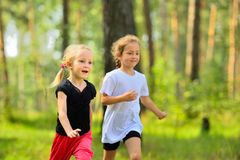 Two little cute girls jogging in forest Royalty Free Stock Photo