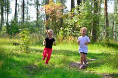 Two little cute girls jogging in forest Stock Image