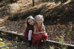 Two little cute girls on lawn in the park. Royalty Free Stock Image