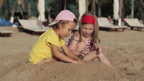 Two little cute girls playing with sand on the beach stock video