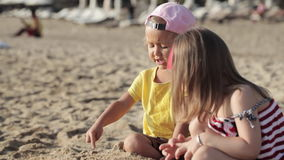 Two little cute girls playing with sand on the beach. Two little cute girls playing together with sand on the beach stock video footage