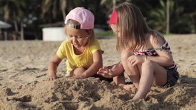 Two little cute girls playing with sand on the beach stock footage