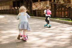 Two little cute girls ride their scooters in the park. Royalty Free Stock Photography
