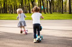 Two little cute girls ride their scooters. In the park in the summer Royalty Free Stock Image