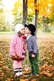 Two little cute kids dating with hand lifts onto shoulder in autmn pa Stock Image