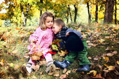 Two little cute kids dating with hand lifts onto shoulder in autmn pa Stock Photos