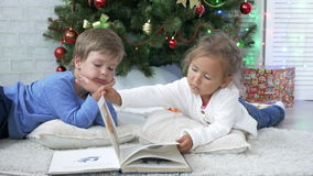 Two little cute siblings reading a book on the floor near Christmas tree stock footage
