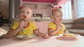 Two little cute twin sisters in yellow T-shirts are eating food together at the table in the kitchen of the house. Two little cute twin sisters in yellow T stock video