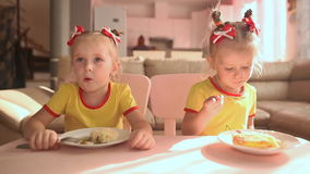 Two little cute twin sisters in yellow T-shirts are eating food together at the table in the kitchen of the house. stock video