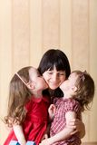 Two little daughter kiss their mother Stock Image