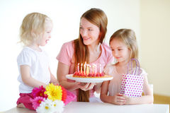 Two little daughters and mom with birthday cake Royalty Free Stock Image