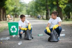 Two little ecologists sitting and collecting plastic rubbish on a blurred park background. Ecology protection concept. Volunteering, charity, cleaning, people Stock Photography