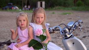 Two little fair-haired girls pose for the camera on the beach. Two little sisters sit together with a pink flower in. On this video you can see as the close-knit stock footage