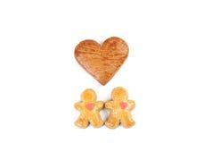 Two little fallen in love gingerbread figure and in between two little figure is one gingerbread heart. Royalty Free Stock Image
