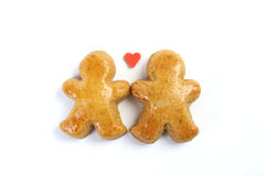 Two little fallen in love gingerbread figure and in between two little figure is one red sweet heart. Royalty Free Stock Images