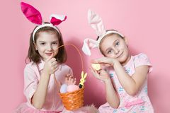 Two little friends, with Bunny ears, depict Easter rabbits. The symbol of Easter.Two girls with ears on their heads and a basket with painted eggs. On a pink stock photo