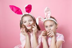 Two little friends, with Bunny ears, depict Easter rabbits. The symbol of Easter.Two girls with ears on their heads and chocolate eggs on a pink background royalty free stock images