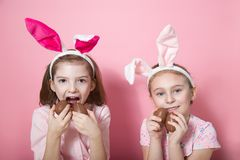 Two little friends, with Bunny ears, depict Easter rabbits. The symbol of Easter.Two girls with ears on their heads and chocolate eggs on a pink background stock photography
