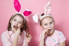 Two little friends, with Bunny ears, depict Easter rabbits. The symbol of Easter.Two girls with ears on their heads and chocolate eggs on a pink background stock image