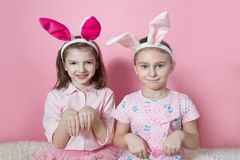 Two little friends, with Bunny ears, depict Easter rabbits. The symbol of Easter.Two girls with ears on their heads. On a pink background stock photography